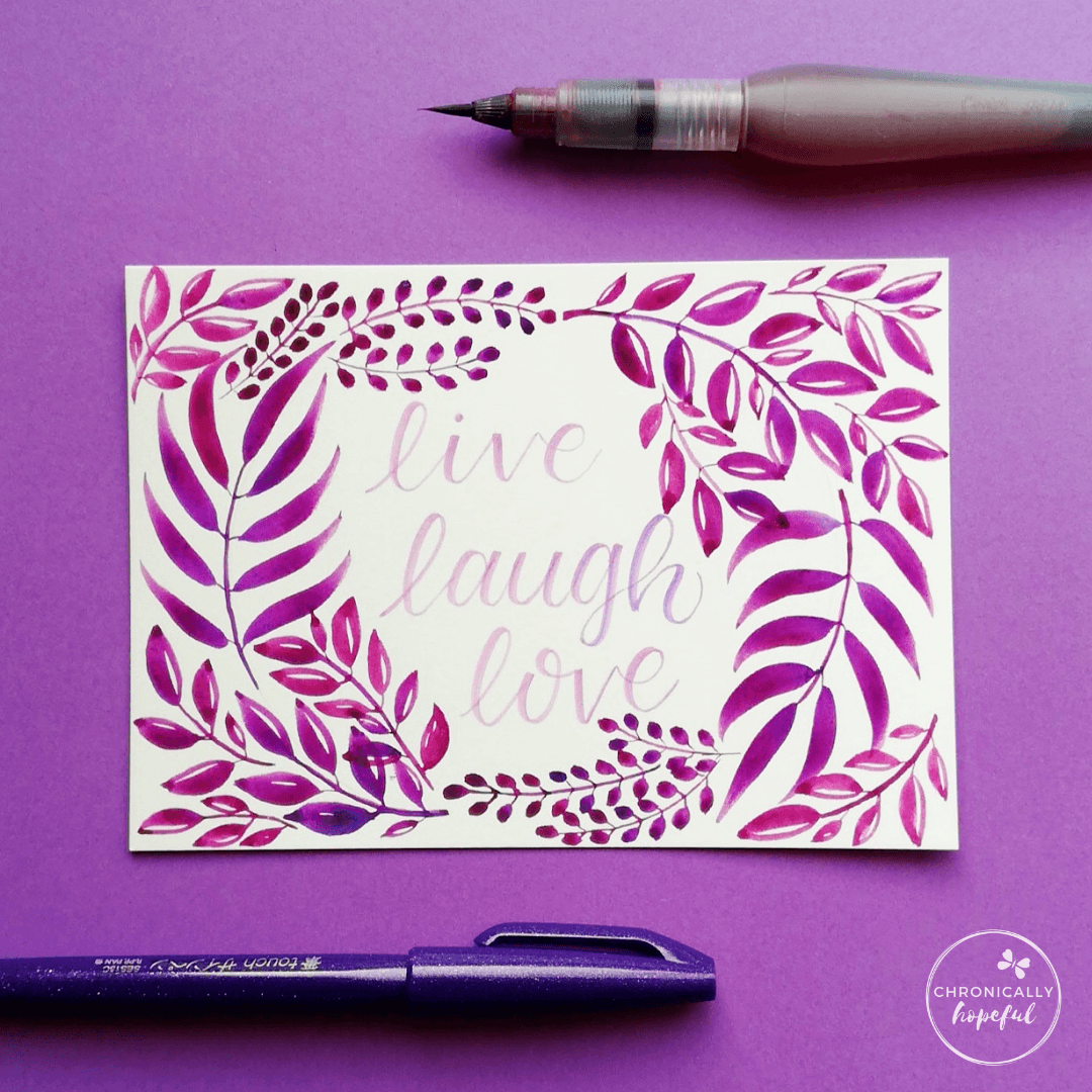 Leafy watercolour composition in purple on white card, the words Live, Laugh, Love lettered in the middle.