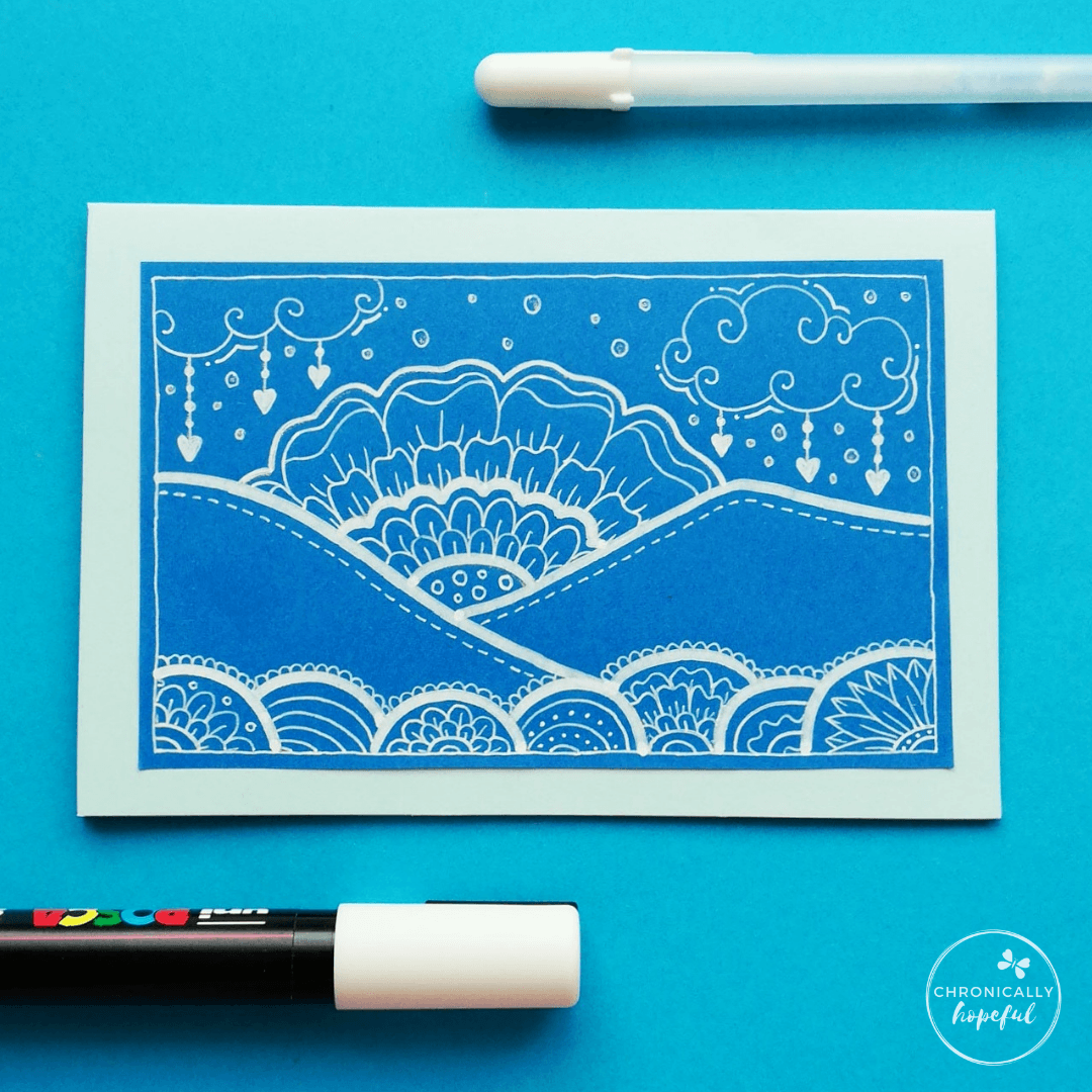 Whimsical scene of hills, sunset and clouds drawn in white paint pen on blue card. 2 pens on the table around the card.