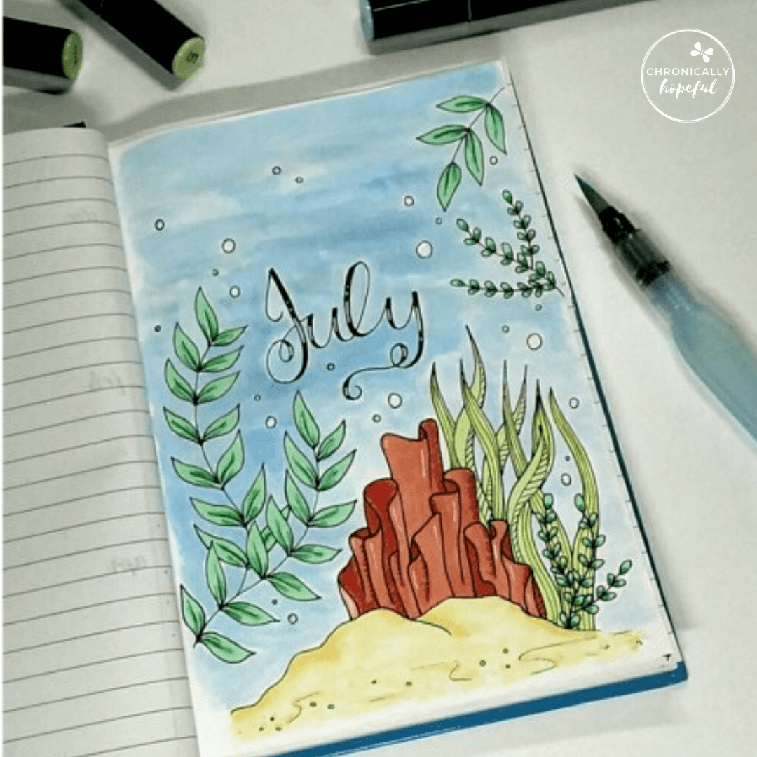 A journal on the table, featuring a cover page for July with an under the sea theme featuring coral and seaweed.
