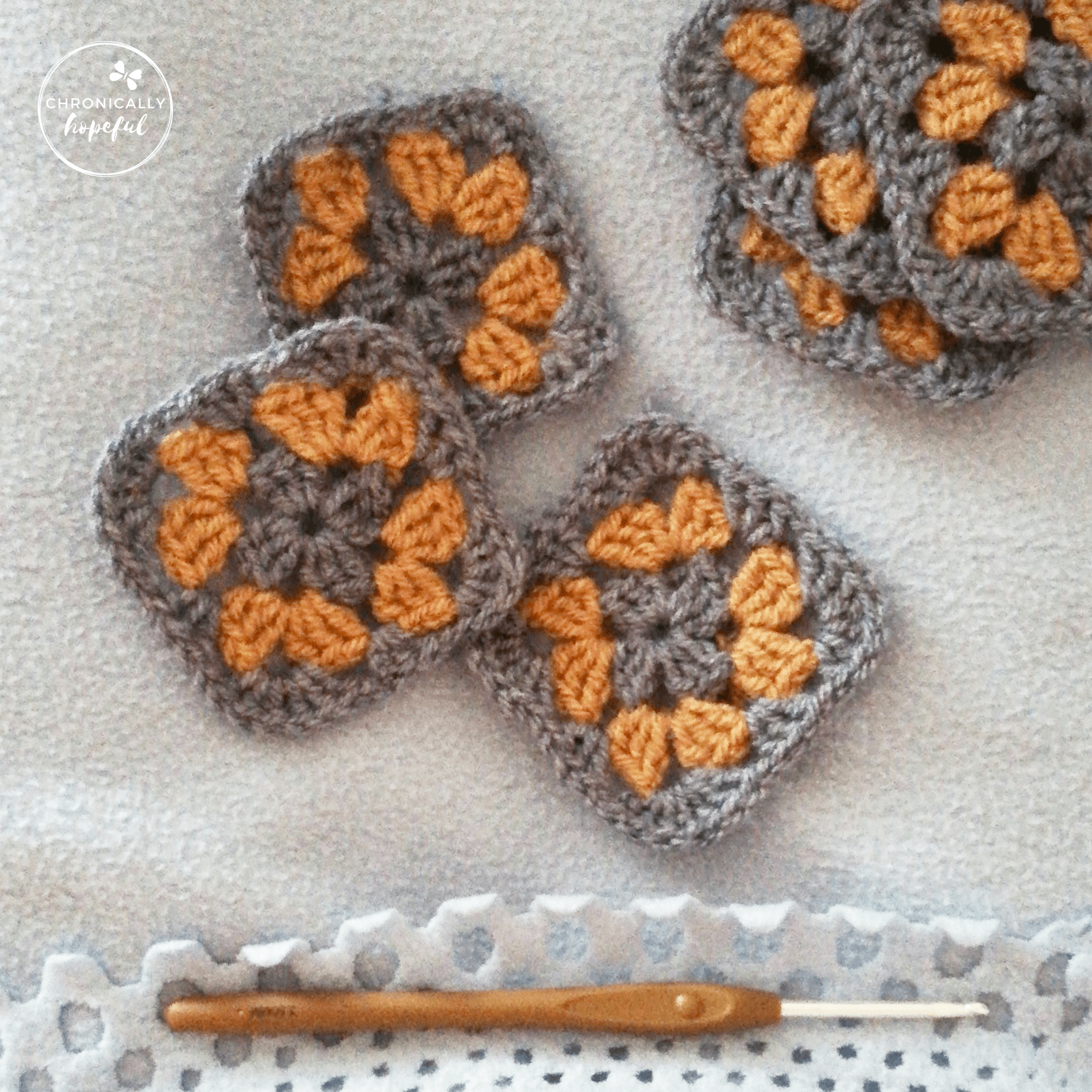 Crocheted granny squares in blue and brown, lying on a blanket. Brown crochet hook to the bottom of the picture.