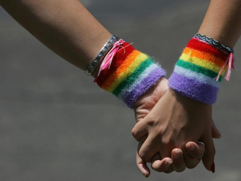 A lesbian couple hold hands during the annual Gay Pride rally in Tel Aviv
