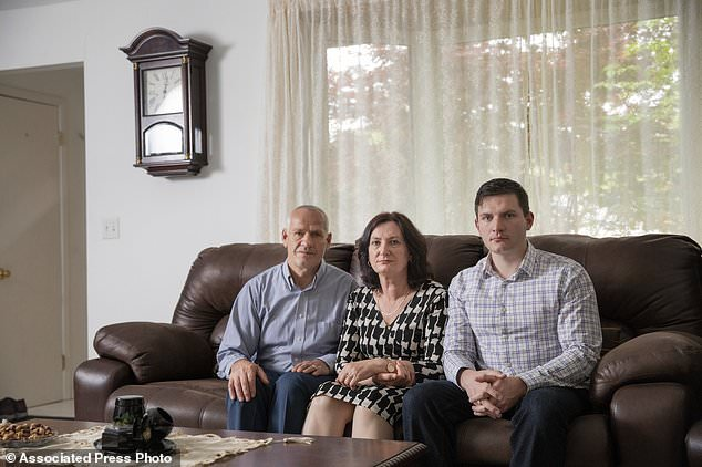In this May 21, 2018, photo provided by the Institute for Justice in Arlington, Va., Rustem Kazazi, from left, his wife Lejla Kazazi and his son Erald Kazazi pose for a portrait in their home in the Cleveland suburb of Parma Heights, Ohio. Rustem Kazazi, a U.S. citizen who immigrated from Albania in 2005, says in a lawsuit filed Thursday, May 31, 2018, that U.S. agents seized his life savings of $58,000 at Cleveland Hopkins International Airport in October 2017, and the government has refused to return the money even though Kazazi faces no charges. A spokesman for the Customs and Border Protection said the agency doesn't comment on pending lawsuits. (Isaac Reese/Institute for Justice via AP)