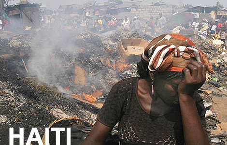 A woman covers her face as smoke billows from a pre-earthquake trash-fir