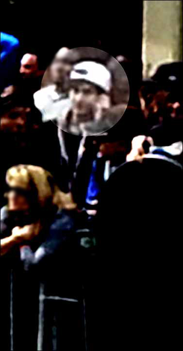 Is the white-hatted suspect on a cell phone? With WHO?