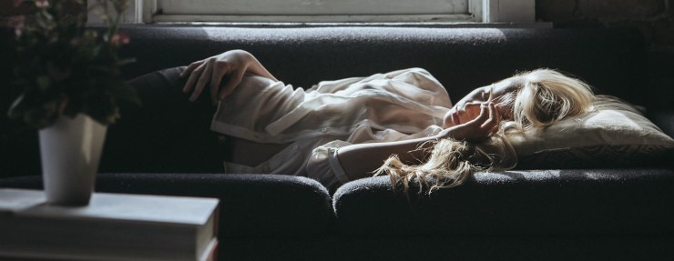 Moody atmosphere, blonde haired woman lays on the couch bathed in dappled sunlight.  She is wearing a sheer material blouse and has one hand resing beside her cheek.  There is a window behind the couch and a vase of flowers infront resting on a book