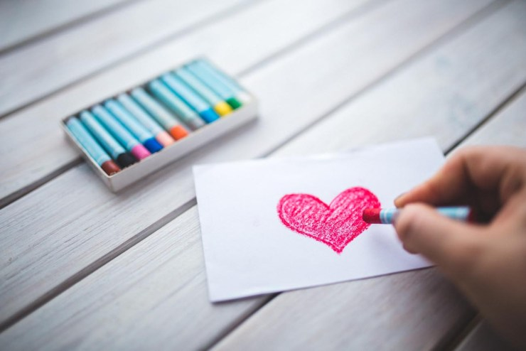 A wooden slatted table with an open box of coloured oil pastel crayons. A hand is shown holding a red crayon and drawing a love heart on a postcard sized piece of paper.