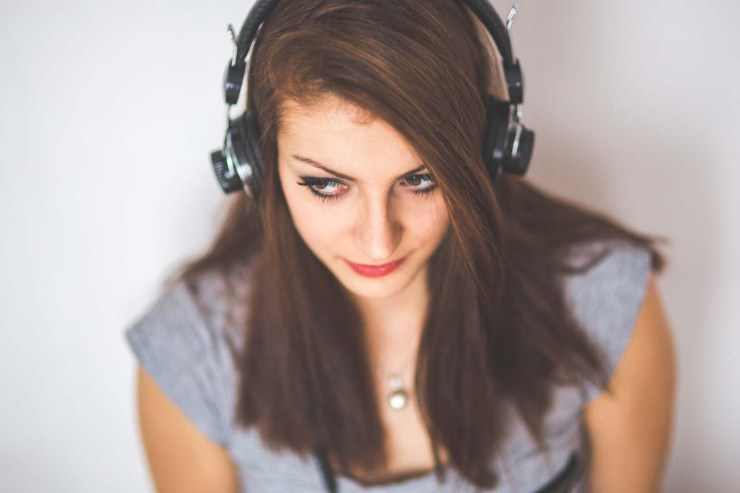 Close up of a woman with long brown straight hair wearing large overear audio headphones.  She is wearing a grey tshirt and silver locket.