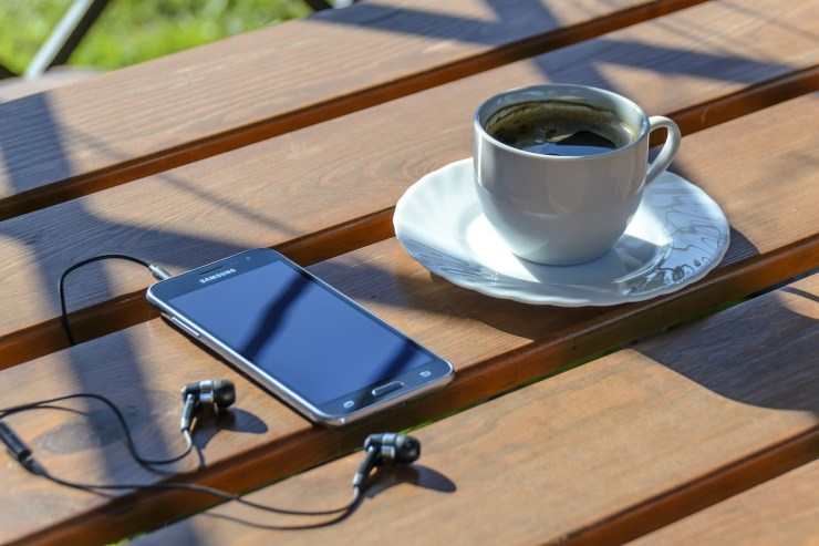 A brown wooden picnic table with a black mobile phone with black earbuds plugged into it and a cup and saucer of black coffee. There is sunlight and shadows on the table.