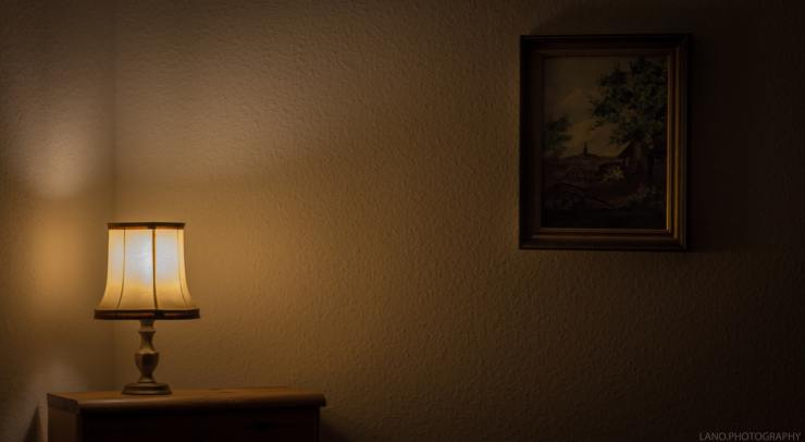 An oldfashioned lamp sits ontop of a small brown cupboard gently illuminating a dark room.  There is a painting of trees and a field on the wall in a wooden frame.
