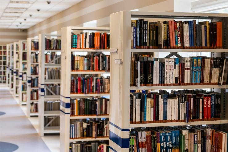 Scene of an aisle in a library with about nine rows of tall shelves filled with books fading into the distance