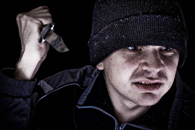 Young angry man with knife on black background