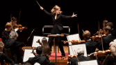 A woman is powerfully leading a large orchestra