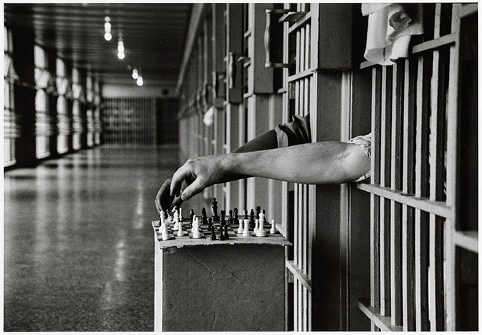 "predecessors: "" Inmates playing chess from between the bars of their prison cells. Photograph by Cornell Capa, 1972. """