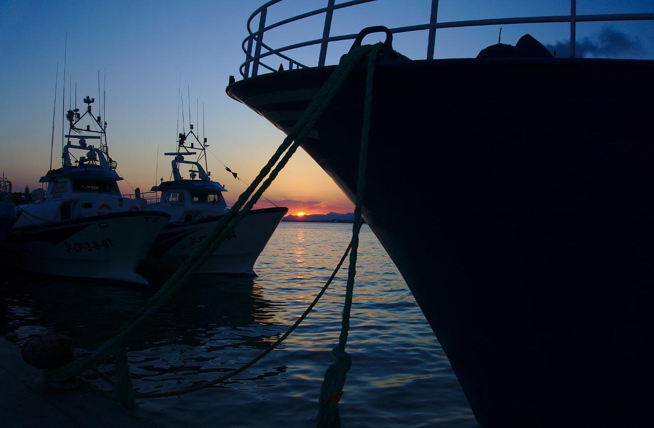 vista de la puesta de sol entre barcos en el puerto de santa pola
