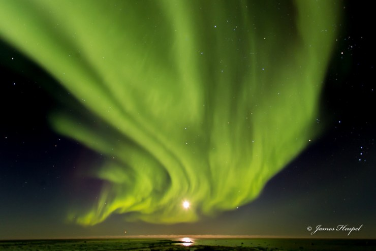 Award-winning photograph of northern lights blanketing full moon over Hudson Bay. Taken by James Heupel at Seal River Heritage Lodge.