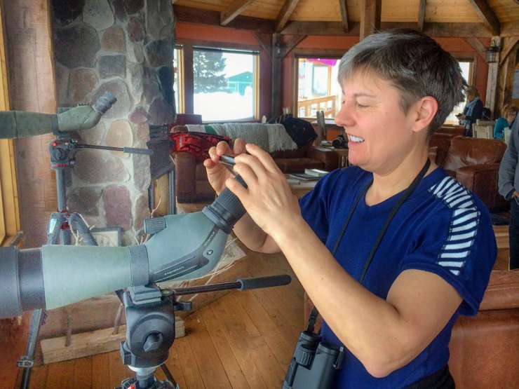 Churchill Wild guest Sue Chadwick photographing wolves through a scope in the lounge at Nanuk Polar Bear Lodge on the Den Emergence Quest. Jad Davenport photo.