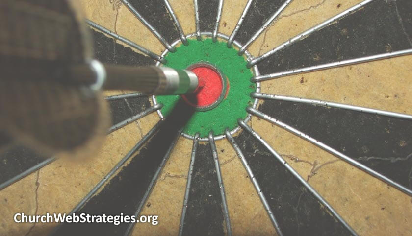 dart hitting dartboard's bulls-eye