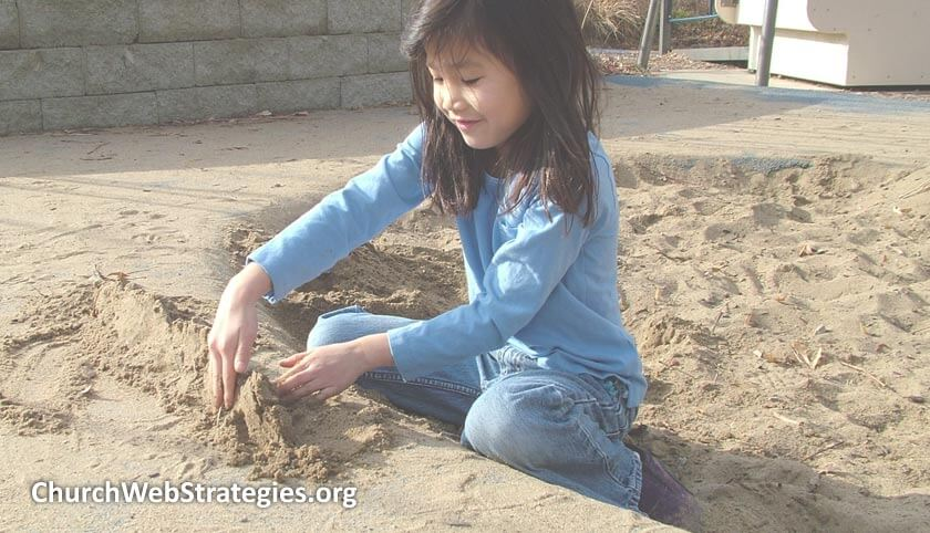 young girl playing in sandbox