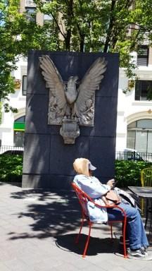 người ngồi xem máy điện tử trước tượng chim ó