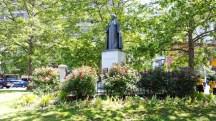 tượng tu sĩ trước YMCA, chung quanh tượng là hàng rào hoa hồng nở thơm ngát.