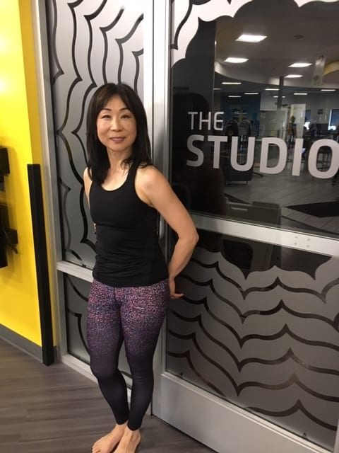 Yuko Caruso, The Studio instructor standing in front of the front door of the heated studio at Chuze Fitness