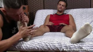 Gay dude rubs his huge cock while his feet are licked