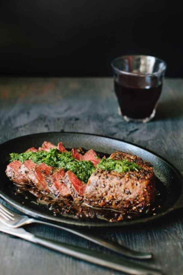 Cast iron skillet with steak chimichurri and a glass of red wine on a rustic table