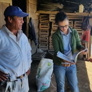"""Carlos Angulo agricultor de Tierra Blanca y la Investigadora Paula Aguilar examinan juntos el """"Manual de Uso de Biobeds"""" elaborado por el CICA"""