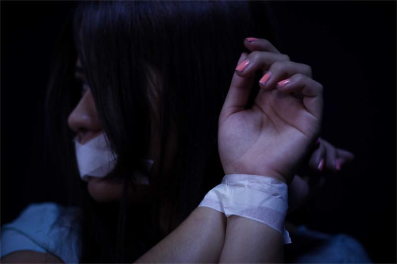 Imagen de mujer atada de manos.