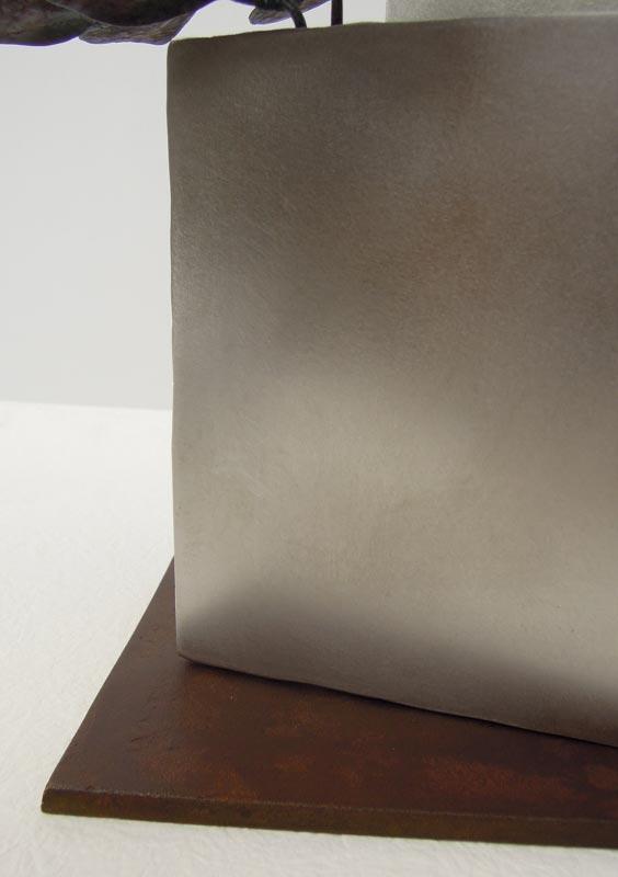 厚みのあるステンレス板の隙間からツルニチニチソウが伸びている様子を鍛鉄で表現したアート作品、ベースのアップ。上品に磨いたステンレス板の柔らかい光沢と、鋳造真鍮板をお歯黒で渋めに染めた色味の対比。