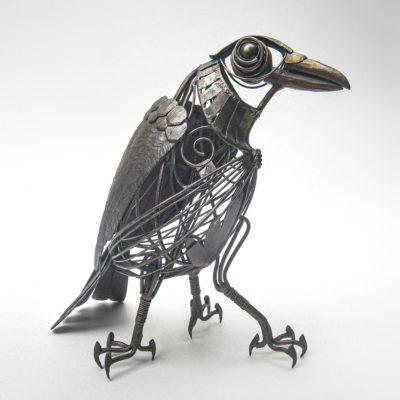 鉄のアートオブジェ。鍛鉄で伝説の生物を制作した幻想的鉄生物 L-Febシリーズ「ヤタガラス」横からの写真。ボディは透け感のあるワイヤー表現、体内にホタル石を持っています。翼は精密に鍛造されたパーツで構成され、三本の足にはしっかりした爪、ソリッドのくちばしと大きな丸い目が特徴的です。