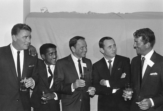 circa 1955:  Members of the Rat Pack (L-R): British actor Peter Lawford (1923 - 1984), American actor, singer, and dancer Sammy Davis Jr. (1925 - 1990), actor and singer Frank Sinatra (1915 - 1998), actor Joey Bishop, and actor and singer Dean Martin (1917 - 1995).  All are wearing dark suits, and all but Bishop are holding drinks.  (Photo by Jack Albin/Hulton Archive/Getty Images)