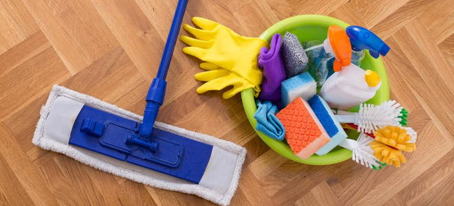 A bucket of cleaning supplies and a mop on a wood floor.