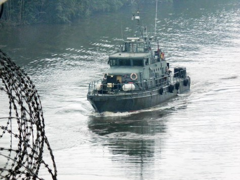 The privately contracted patrol boat NNS WARRIOR provides riverine escort to a merchant vessel in 2016. Photo: source withheld.