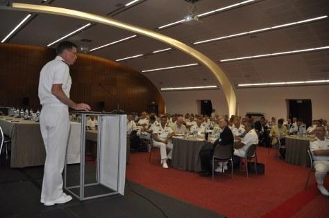 A presenter speaks before gathered leaders. (STRIKFORNATO)