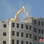 Visioni inusuali dalla Cina: una ruspa sul tetto tenta di abbattere un palazzo