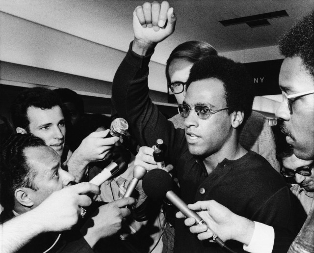 Huey P. Newton, Black Panther party minister of defense, raises his arm as he is literally surrounded by newsmen and others at Philadelphia's International Airport on Friday, Sept. 4, 1970 in Philadelphia upon his arrival for a three-day convention. Man at right is not identified. (AP Photo/Rusty Kennedy)