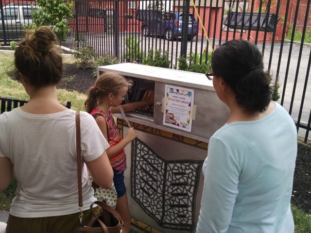 Girl using the new little free library Photo: Angela Ginty
