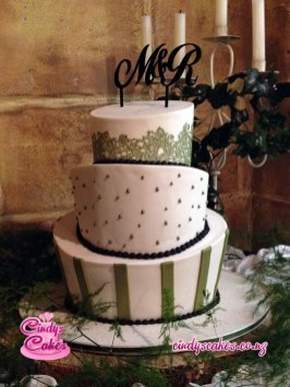 3 tier Wonky white with green trimming wedding cake with the letters M&R as the topper