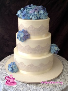 A 3 tier white wedding cake with blue sugar blossom and a lace texture.