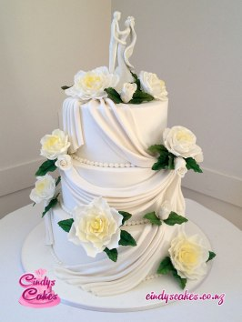 Wedding cake with yellow sugar flowers and sugar cloths draped across the 3 tiers. It is topped with a bride and groom.