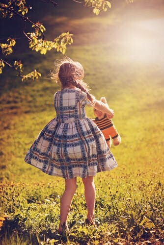 A little girl walking across a lawn with a teddy bear in her arms.