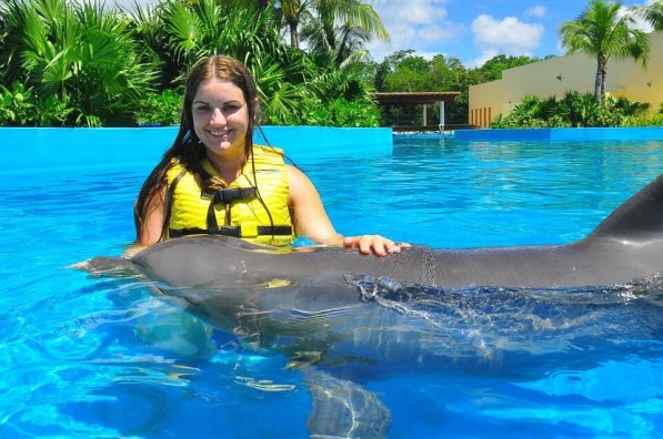 Katy swimming in a pool with a dolphin.