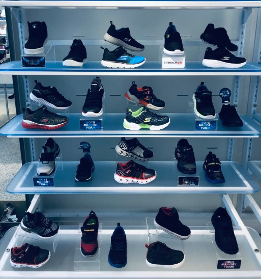 A variety of running shoes for a baby boy.