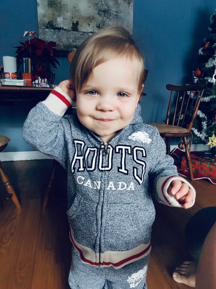 Cherie's toddler wearing a Roots sweatshirt standing near Christmas tree.