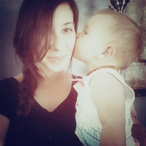 Cherie with her hair braided and her daughter standing beside her kissing her cheek.