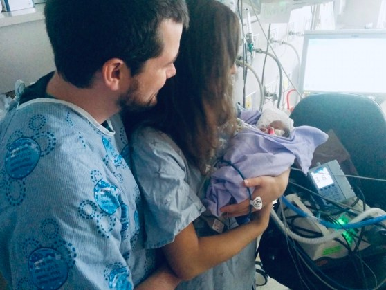 Jami and Mike holding newborn twin in hospital.