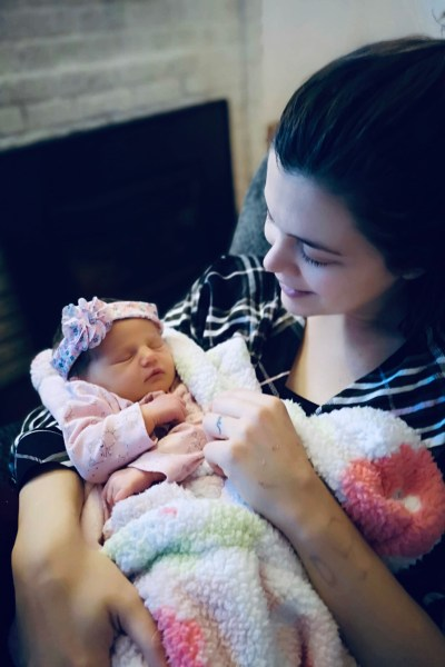 Mom smiling at new born baby daughter, who is dressed in pink.