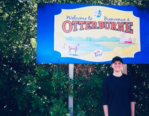 "A young man standing in front of a sign that says, ""Welcome to Otterburne."""