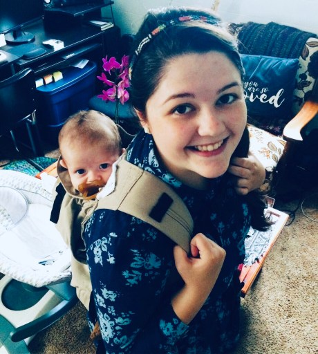A mom holding a baby on her back in a carrier.